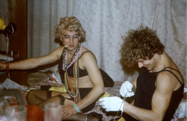 Colour photograph of two young smiling men. They are wearing make up, skimpy women clothes, jewellery and short curly wigs. It looks like it was taken at the party.