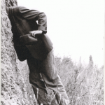 """Black and white """"Not secret"""" zine cover. Photograph of a man holding a hat with his head in some rocks."""