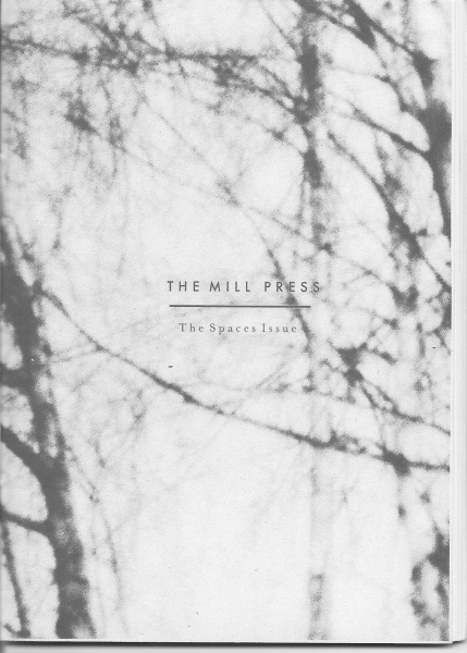 """Grey and black """"The Mill press"""" the spaces issue zine cover with small printed title text in 2 fonts over an out of focus photograph of bare branched trees."""