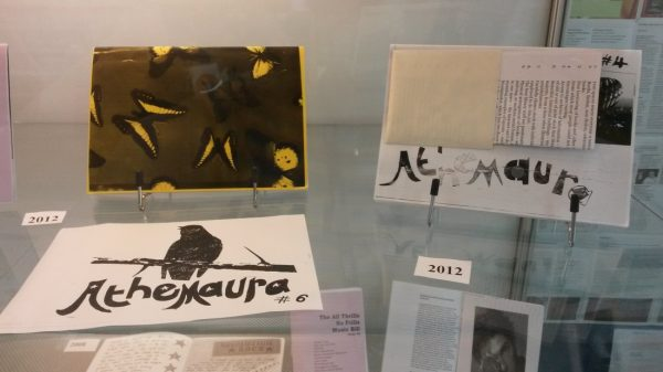"""Colour photograph of """"Athemaura"""" zine material in a glass display cabinet."""