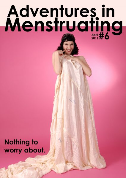 """Colour """"Adventures in menstruating"""" issue 6 zine cover. Photograph of a woman in a flowing fabric sheet on a pink background with black text."""