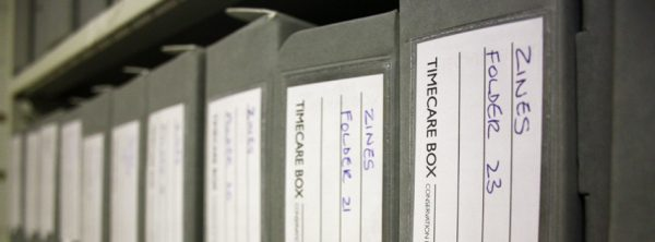 Colour photograph of a row of grey archive  boxes of zines with handwritten labels.