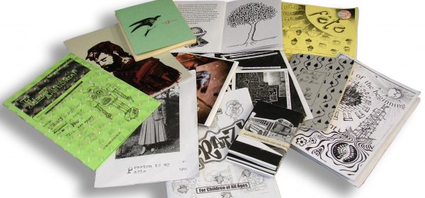 Colour, mostly black, white and green. Photograph of a pile of illustration zines.