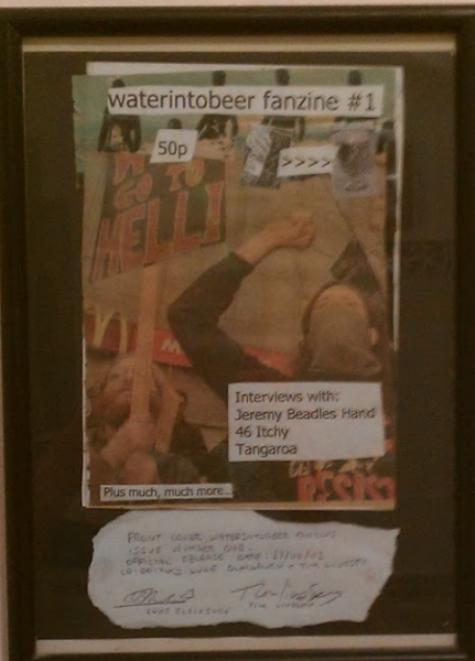 """Colour """"Water into bear"""" issue 1 cover.  Collage of protesters with placards and cut and paste text of zine title."""