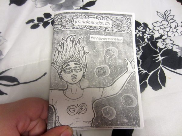 """Hand holding zine """"(meta)paradox #5 the neuroqueer issue"""". Cover shows title and drawing of person seemingly floating among bubbles."""