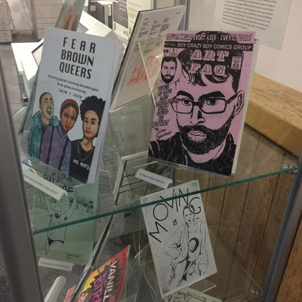 A selection of zines in a glass vitrine display case including zine titles: Art Fa, Fear Brown Queers, and Moving.