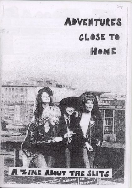 Cover image of Adventures close to home: a zine about the Slits.  Text is hand drawn in black bold.  Black and white background image of a road flyover and flats behind.  In the front is a black and white cut out image of The Slits.